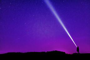 Person with flashlight illuminating the night sky.