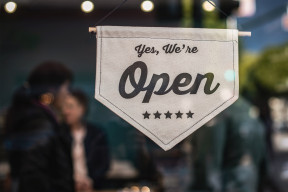Shop window banner saying Yes, we're open