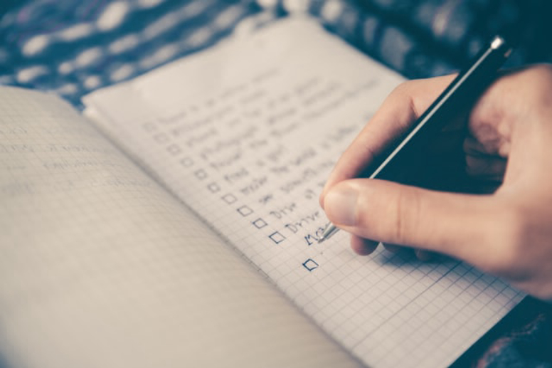 Person writing down a list of things in a notebook.
